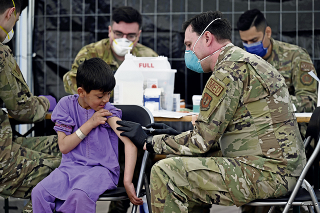 A U.S. Air Force Airman administers mumps, measles and rubella, and chickenpox vaccines to a child evacuee awaiting onward travel at Ramstein Air Base, Germany, Sept. 18, 2021. Ramstein established two centers where evacuees can volunteer to receive the vaccine to protect them from contracting MMR and varicella. Medical professionals administered varicella and MMR vaccines to more than 3,000 evacuees on the first day of mass vaccinations. (U.S. Air Force photo by Tech. Sgt. Devin Nothstine)